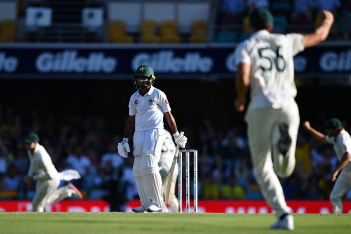 Pakistan's batsman Asad Shafiq (C) reacts after his dismissal as Australia's players celebrate on day three of the first Test cricket match between Pakistan and Australia at the Gabba in Brisbane (AFP Photo)