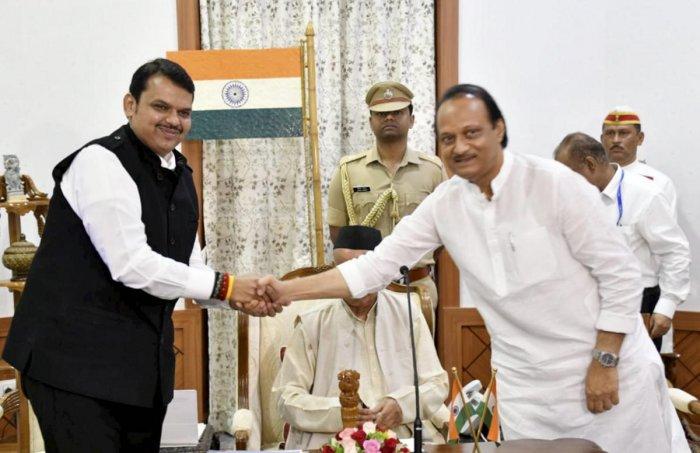 Chief Minister of Maharashtra Devendra Fadnavis shakes hands with his Deputy Chief Minister Ajit Pawar. (PTI Photo)