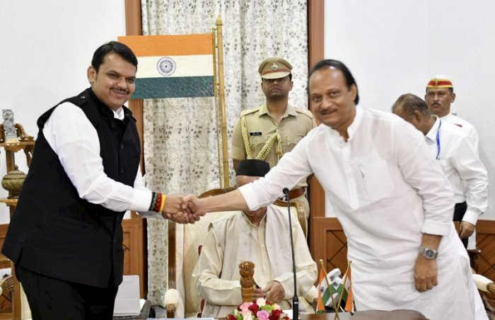 Newly-sworn in Chief Minister of Maharashtra Devendra Fadnavis shakes hands with his Deputy Chief Minister Ajit Pawar. (PTI Photo)