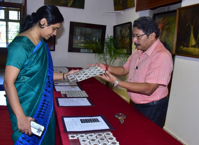 Numismatist Krishna Prasad Rai explains about his collection to Deputy Commissioner Sindhu B Rupesh at the exhibition of coins held at Srimanthi Bai Memorial Government Museum in Bejai.