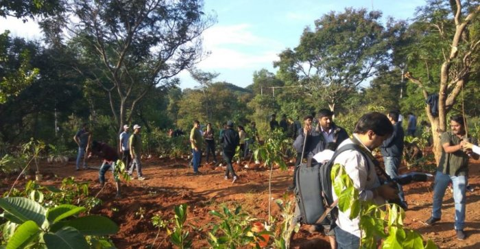 Volunteers at the plantation drive at the bio-park in Bangalore University on Saturday. SPECIAL ARRANGEMENT