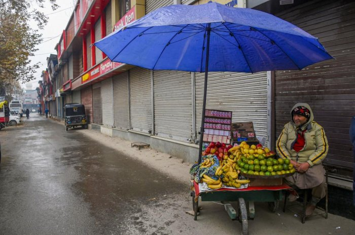 A vendor sells fruits outside closed shops at market during shutdown in Srinagar, Thursday, Nov. 21, 2019. The shutdown was intensified a day after threatening posters appeared in the many parts of the Valley. Photo/PTI