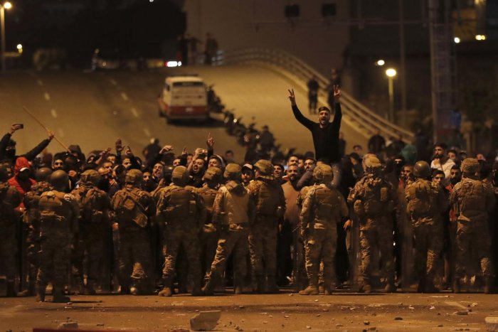 Supporters of the Shiite Hezbollah and Amal Movement groups shout slogans as they stand in front of Lebanese army soldiers after a clash erupted between the anti-government protesters and them, in Beirut, Lebanon. (AP Photo)