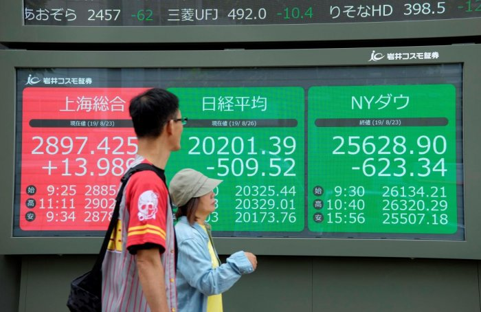 Pedestrians walk in front of an electric quotation board displaying the numbers oF the Nikkei 225 index at the Tokyo Stock Exchange (C), the Shanghai Stock Exchange (L) and New York Dow (R) in Tokyo on August 26, 2019. (AFP Photo)