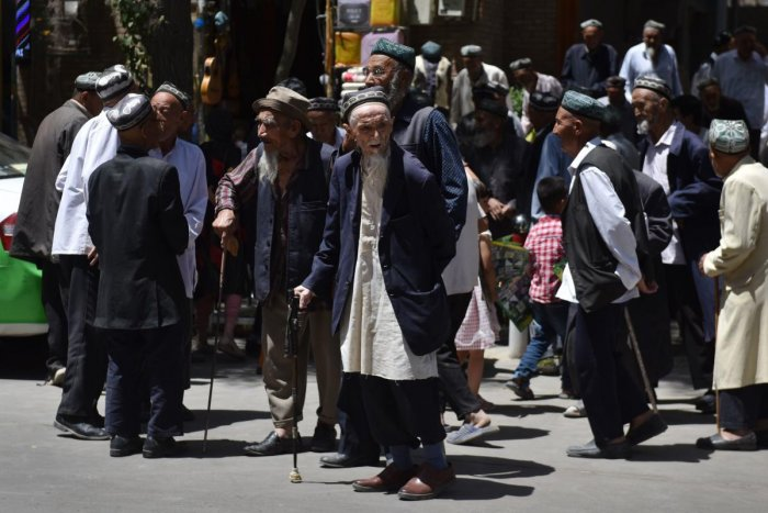 Uighur men are seen leaving a mosque after prayers in Hotan in China's northwest Xinjiang region. (AFP Photo)