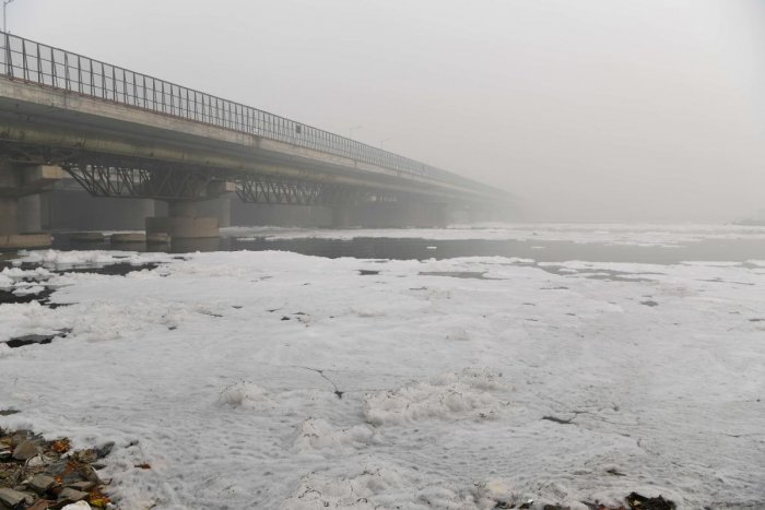 Foam is seen floating along the Yamuna river near a bridge amidst heavy smog conditions, in New Delhi. AFP