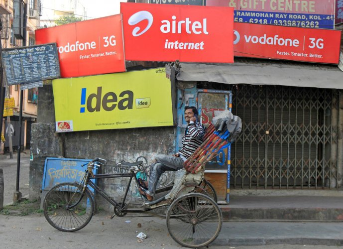 A rickshaw puller speaks on his mobile phone in front of advertisement billboards belonging to telecom companies. Photo by REUTERS