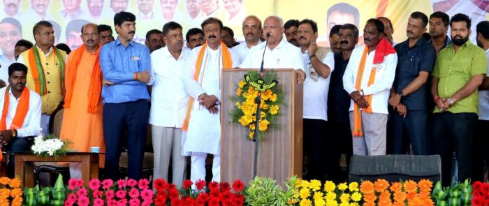 Chief Minister B S Yediyurappa addresses the people, at Kikkeri, in K R Pet taluk on Monday. BJP candidate K C Narayana Gowda is also seen.