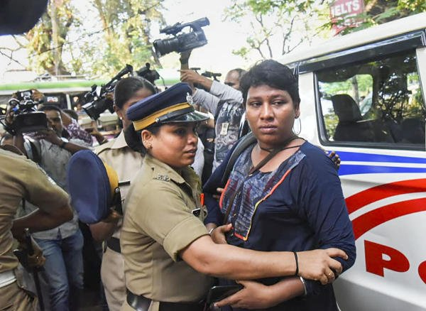 Activist Bindu Ammini is being escorted by police after a protest by various Hindu organizations outside police commissioner's office, in Kochi, Tuesday, Nov. 26, 2019. (PTI photo)