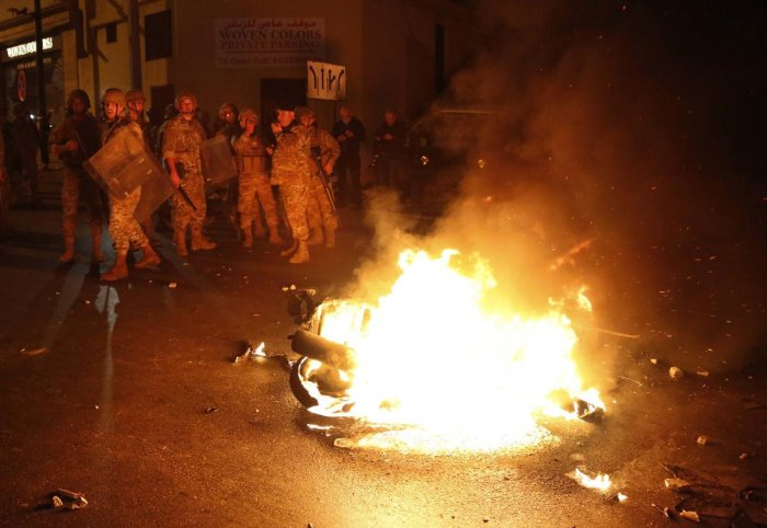 Lebanese army soldiers stand near a motorcycle that was set on fire by protesters. (AP Photo)