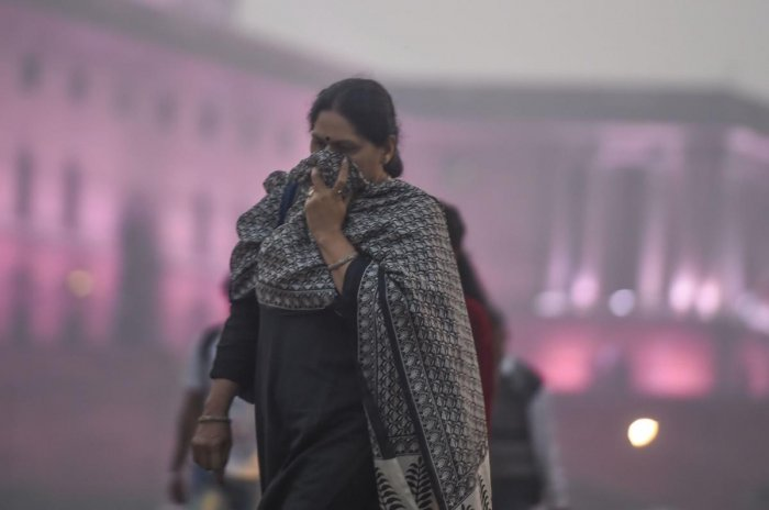 Pedestrian cover their face amid heavy smog as the air quality further dips to 'severe' category. PTI
