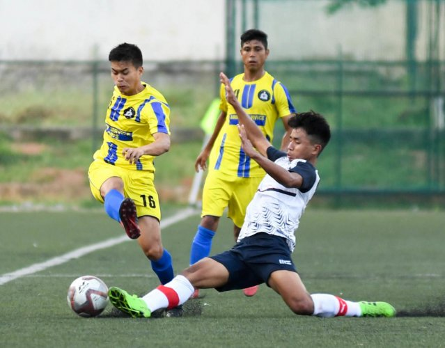 Lethaolen Khongsai of MEG FC (centre) and Oinam Gautham Sing of ASC FC vie for the in the Super Division game on Tuesday. DH PHOTO/BH SHIVAKUMAR