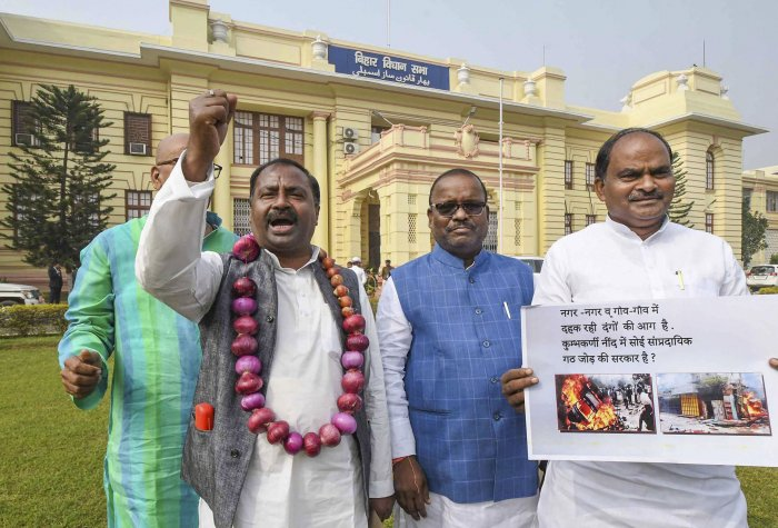 RJD MLA Shiv Chandra Ram raise slogans during a demonstration against the government for failing to control soaring prices of onions during the ongoing Winter Session of Bihar Assembly, in Patna. (PTI Photo)