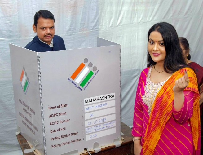 Former Maharashtra Chief Minister and Nagpur BJP candidate Devendra Fadnavis casts his vote while his wife Amruta shows her inked finger after casting vote during the Maharashtra Assembly elctions, in Nagpur. (PTI Photo)