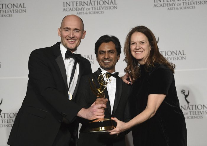 """Executive producer/director/writer James Watkins, left, actor Nawazuddin Siddiqui and executive producer Dixie Linder pose with the best drama series award for """"McMafia,"""" during the 47th International Emmy Awards. (PTI Photo)"""