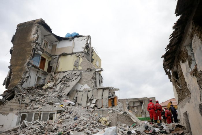 Emergency personnel stands on debris of collapsed and damaged buildings following Tuesday's powerful earthquake in Thumane, Albania. Photo by REUTERS