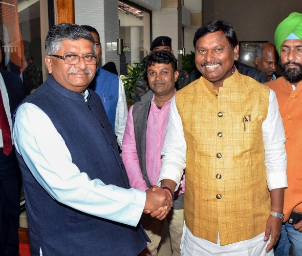 IT and Telecom Minister Ravi Shankar Prasad(L) shakes hands with Union Tribal Affairs Minister Arjun Munda during the release of BJP manifesto for Jharkhand Assembly Elections-2019, in Ranchi. (PTI Photo)