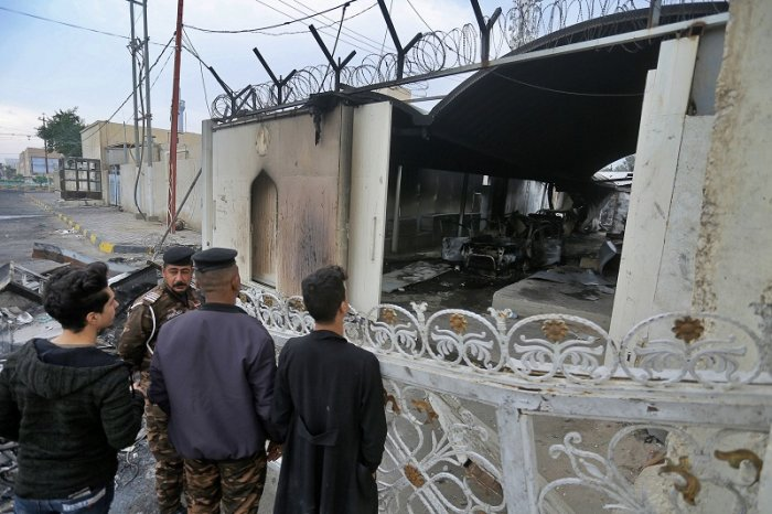 Security force and civilians gather near the burned Iranian consulate in Najaf, Iraq. (PTI Photo)