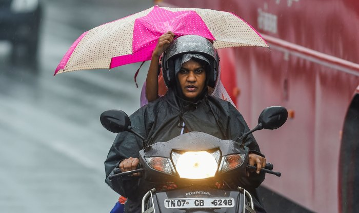 Motorists ride a bike during heavy rainfall following the onset of North East Monsoon across the state, in Chennai. (PTI Photo)