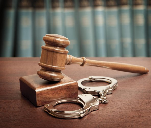 Gavel and handcuffs on wooden background. DH photo