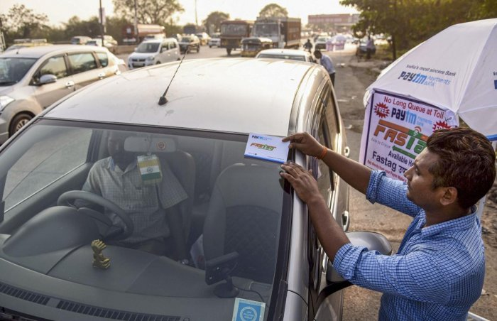 A worker fixes a FASTag sticker on the windscreen of a car. (PTI Photo)