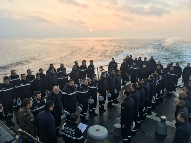 French sailors stand during a minute of silence on board Marine Nationale ship Commandant Birot (Aviso Type - Classe d'Estienne d'Orves) at an undisclosed location in The Black Sea, early November 28, 2019, as they remember the thirteen French soldiers killed when two helicopters collided during Operation Barkhane in Mali. (AFP Photo)