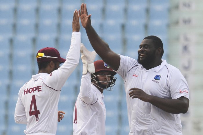 West Indies' Rahkeem Cornwall (R) celebrates with teammates after a dismissal during the second day of the only cricket Test match between Afghanistan and West Indies at the Ekana Cricket Stadium in Lucknow. Photo/AFP