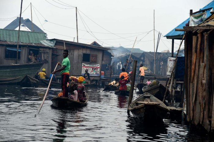 A boy stands on a canoe as part of his daily routine in the Makoko waterfront settlement in Lagos, on October 23, 2019. - Code for Africa, an aid group that is using drones and young slum dwellers to map Makoko at the heart of Nigeria's economic capital. (AFP Photo)