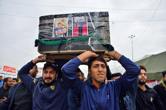 Young Iraqis carry a coffin of an anti-government demonstrator killed during protests a day earlier, during a funeral procession in the central holy shrine city of Najaf. Nearly 45 people were reportedly killed and hundreds wounded across Iraq yesterday,