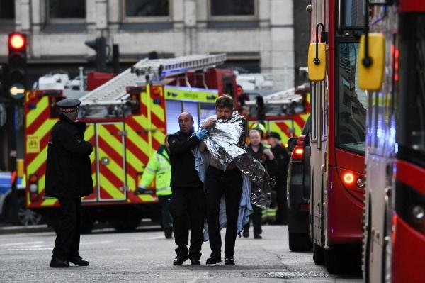 Police assist an injured man near London Bridge in London, on November 29, 2019 after reports of shots being fired on London Bridge. (AFP photo)