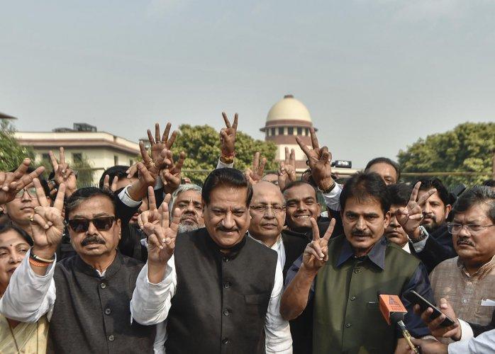 Senior Congress leaders Prithviraj Chavan, Abhishek Singhvi, KC Venugopal, Shiv Sena MP Gajanan Kirtikar and others display victory sign at the Supreme Court of India during a media interaction, in New Delhi, Tuesday, Nov. 26, 2019. (PTI Photo)