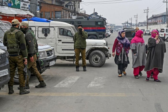 Security personnel stand near the site of a grenade blast as residents walk on a roadside at a market place outside the campus of Kashmir's main university in Srinagar on November 26, 2019. (AFP Photo)