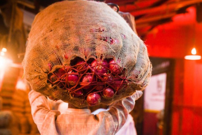 A labourer carries a sack of onions on is head as he makes his way in a market in Kolkata on November 29, 2019. (AFP Photo)
