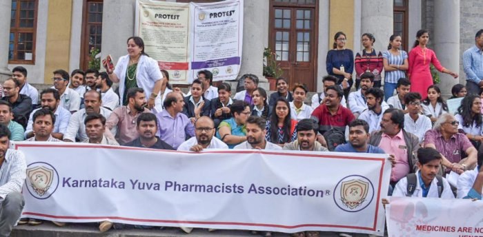 Pharmacists and students from various colleges in the city staged a protest at Town Hall on Friday. DH photo