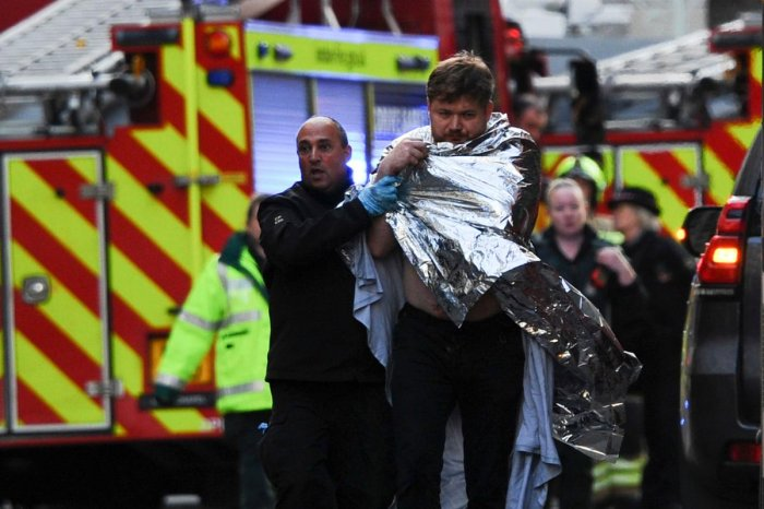 Police assist an injured man near London Bridge in London, on November 29, 2019 after reports of shots being fired on London Bridge. - The Metropolitan Police on Friday said several people were injured and a man was held after a stabbing near London Bridge in the centre of the British capital. (AFP Photo)