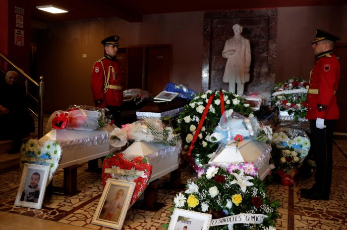 Military members stand guard next to the coffins of eight members of the Lala family, who were killed during an earthquake that shook Albania, in Durres, Albania. (Reuters Photo)