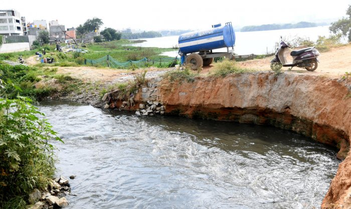 Water from Madivala lake moves through the strome water drain after the water leavel increased due to inflow of the water from Hulimavu lake bleached in Bengaluru. (DH file photo)