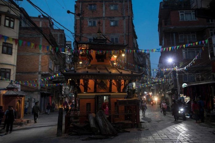 A devotee looks out from a Hindu temple nested between two street in Kathmandu (Photo AFP)