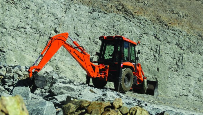 A backhoe loader of Tata Hitachi is in action at a quarry