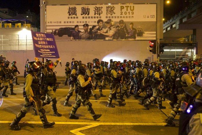 Riot policemen hold aloft a warning banner as they advance along a road in Hong Kong, Saturday, Nov. 30, 2019. (PTI Photo)