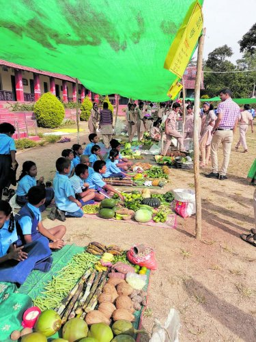 Students of the Government High School in Ankanahalli near Shanivarasanthe sell vegetables during 'Makkala Santhe'.