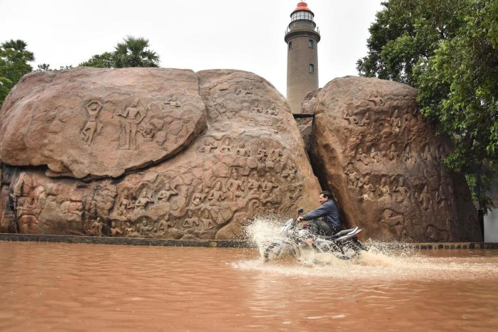 A man rides a motorcycle through a waterlogged road after heavy rains, at the heritage site of Mamallapuram