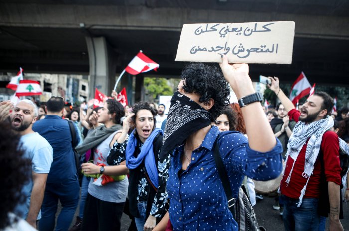"""A Lebanese anti-government protester holds up a sign reading """"all means all, including harassers"""", during a demonstration march on the former demarcation line separating Beirut. (AFP Photo)"""