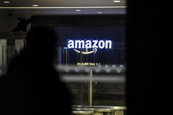An employee enters the Amazon France headquarters in Clichy, north of Paris, early on November 29, 2019, as Attac movement activists protest in front of the entrance during an anti Black Friday action. (AFP Photo)