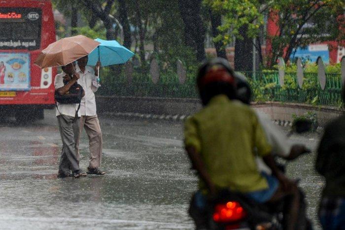 Pedestrians holding umbrellas cross a road during heavy rain in Chennai (AFP Photo)