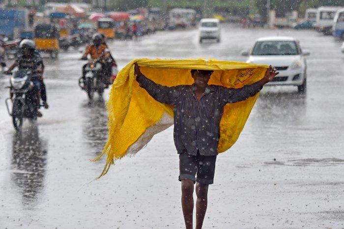 A boy covers himself with a plastic sheet as rain lashed several parts of the city, near Marina beach in Chennai. (PTI Photo