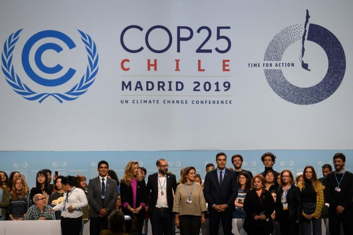 Spanish Prime Minister Pedro Sanchez (C-R) and Spanish Minister for Ecological Transition Teresa Ribera (C-L) pose with volunteers onstage as they visit the congress centre IFEMA in Madrid on November 30, 2019, where the COP25 climate summit will be held