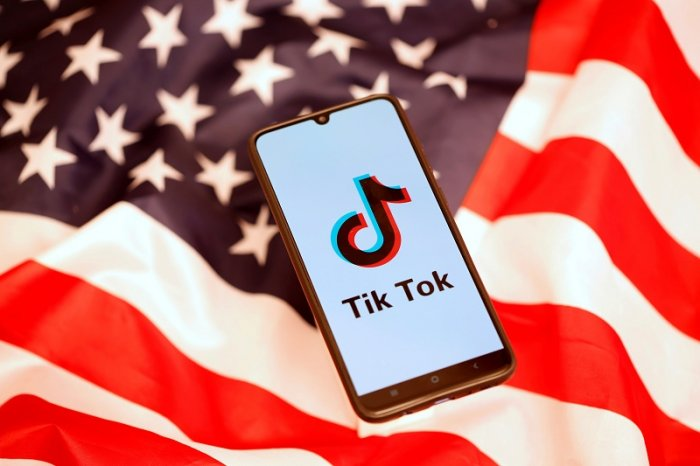 TikTok logo is displayed on the smartphone while standing on the US flag in this illustration picture taken. (Reuters Photo)