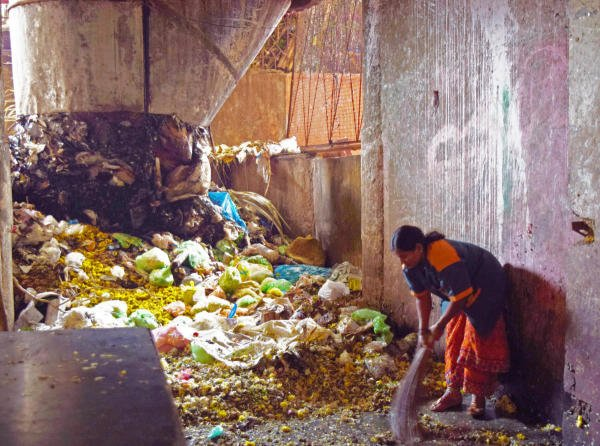 A BBMP Worker cleaning a huge pile of garbage that reeks of feaces and rotten flowers inside City Market on a Monday afternoon. (DH Photo/Sneha Sengupta)