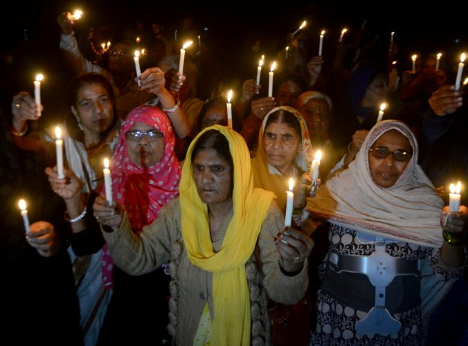 Women hold candles during a vigil to mark the 35th anniversary of the Bhopal gas disaster, in Bhopal. (Reuters photo)